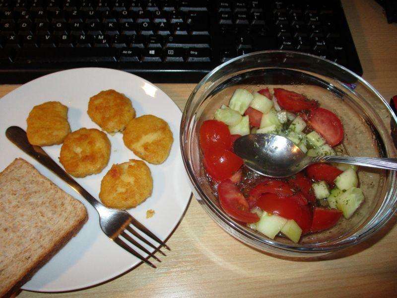 Куринные нагится и салат из помидор и огурцов
